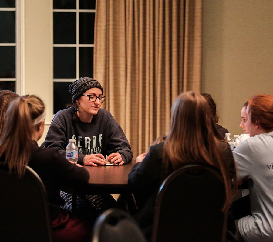 woman sharing with small group of students